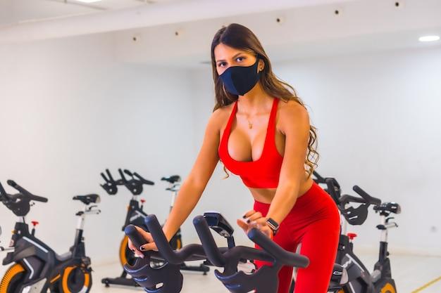 Pandemia de coronavirus. chica entrenando en bicicletas estáticas, gimnasios con capacidad reducida, distancia social y una nueva normalidad