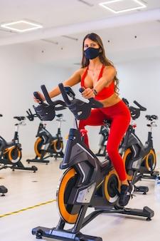 Pandemia de coronavirus. chica entrenando en bicicletas estáticas con mascarilla, gimnasios con capacidad reducida, distancia social y una nueva normalidad