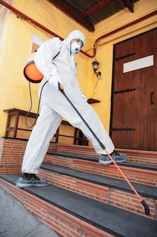 Pandemia de coronavirus. desinfectante en un traje protector y mascarilla rocía desinfectantes en la casa u oficina