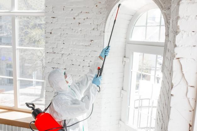 Pandemia de coronavirus un desinfectante con traje protector y mascarilla rocía desinfectantes