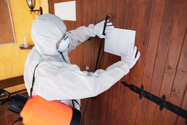 Pandemia de coronavirus un desinfectante con traje protector y mascarillas en aerosol
