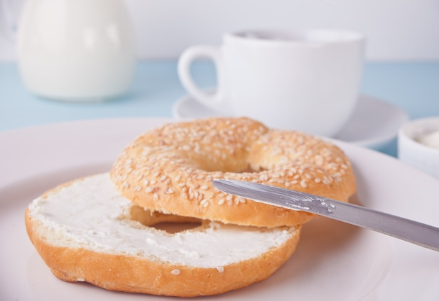 Panecillo sano fresco en una servilleta blanca con la taza de café, de queso cremoso y de huevos para el desayuno.