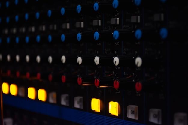 Panel de control del mezclador de sonido sobre fondo claro oscuro en la sala de control de audio.