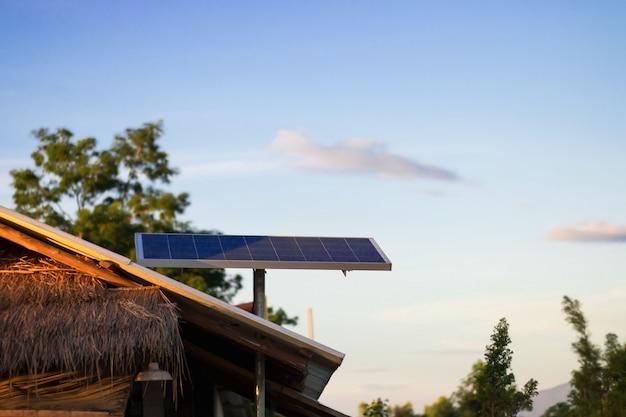 Panel de energía solar o fotovoltaico en el techo de una casa en el campo y el cielo azul
