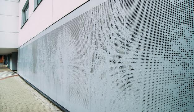 Panel perforado abstracto de metal gris. patrón de árboles