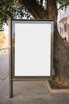 Panel publicitario cerca del árbol