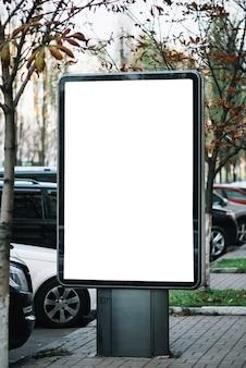 Panel publicitario cerca de autos en el estacionamiento