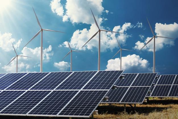 El panel solar del concepto de energía de energía limpia con turbina de viento y fondo de cielo azul