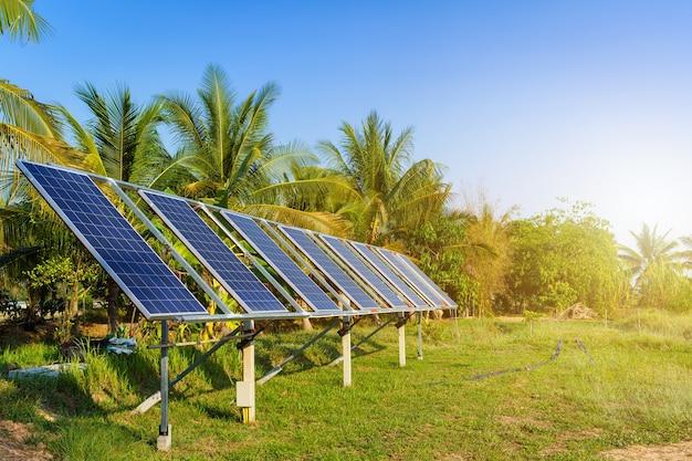 Panel solar de energía para la agricultura en un área de casas rurales campos agrícolas fondo de cielo azul, agroindustria del hogar estilo rural en tailandia, concepto de energía verde limpia alternativa de granja inteligente