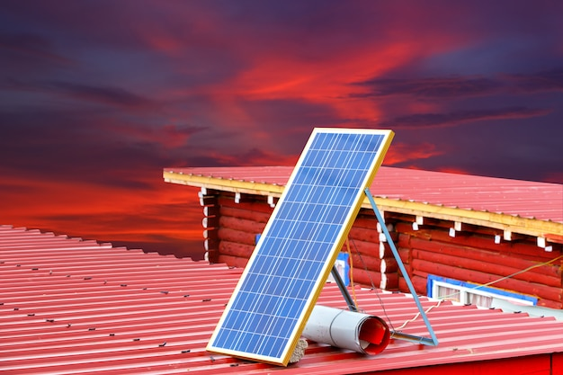 Panel solar en un techo rojo en larung gar (academia budista) en sichuan y cielo rojo