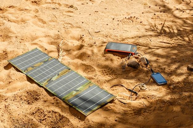 Panel solar tendido en el suelo y carga el teléfono