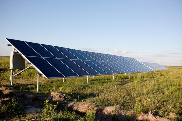 Paneles solares, cielo azul y campo verde.