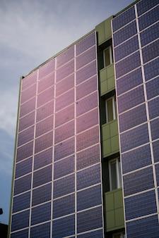 Paneles solares para generar electricidad en la pared de un edificio industrial en la ciudad durante el día