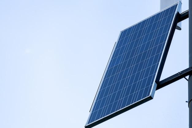 Paneles solares en pilar contra el fondo del cielo. luz pública de la ciudad con panel solar encendido con cielo azul con nubes