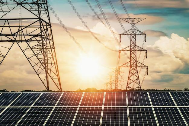 Paneles solares con pilón de electricidad y puesta de sol.