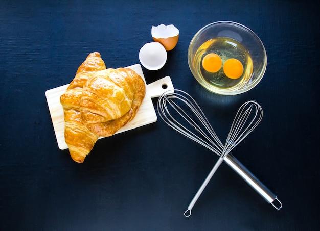 Panes caseros o bollo en el fondo de madera, croissant hojaldre, comida de desayuno