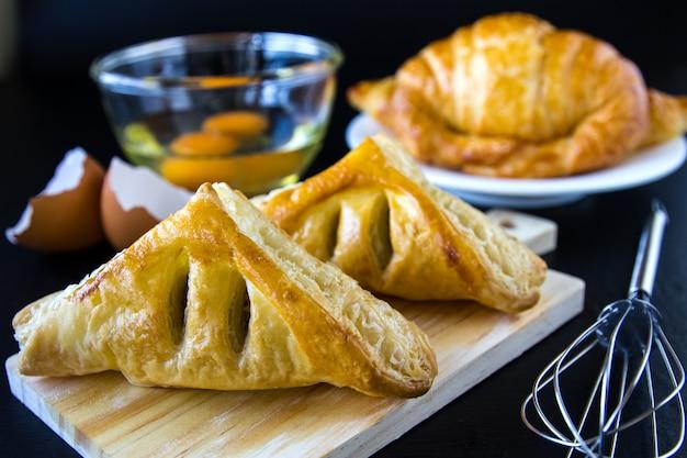 Panes caseros o bollo en el fondo de madera, croissant hojaldre y pasteles, comida de desayuno