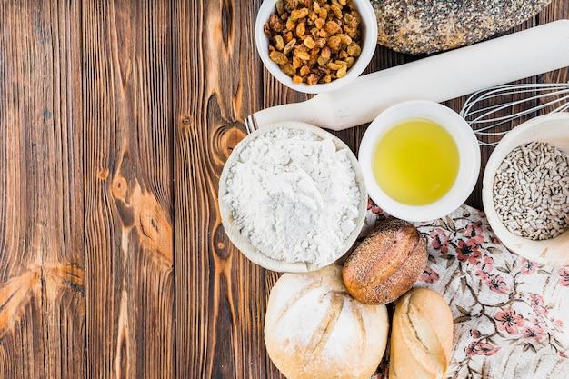 Panes con ingredientes, rodillo y bigote en la mesa de madera