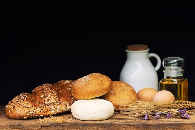 Panes, leche y aceite en la tabla de madera con el fondo negro.