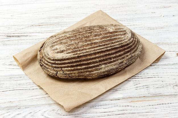 Panes de pan de centeno sobre fondo de madera con bolsa de papel