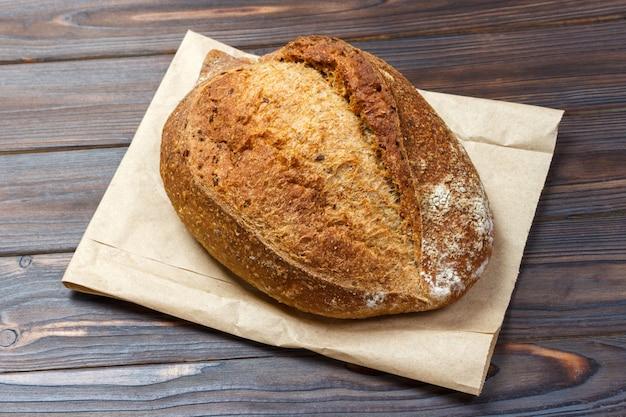 Panes de pan fresco en la mesa de madera con bolsa de papel. vista superior