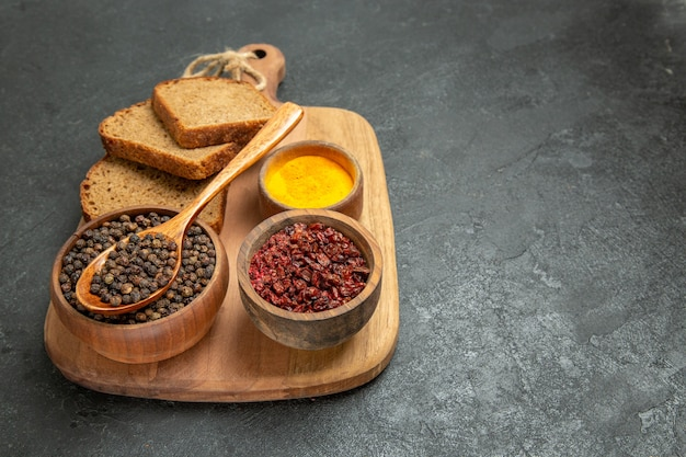 Panes de pan de vista frontal con condimentos sobre fondo gris comida de pan especia caliente