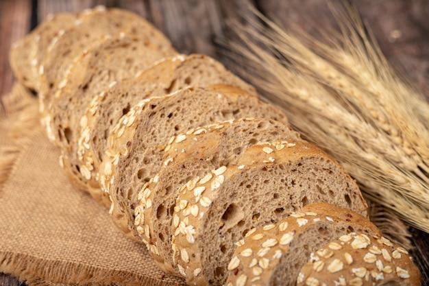 Panes rebanados y pasto de trigo en el saco.