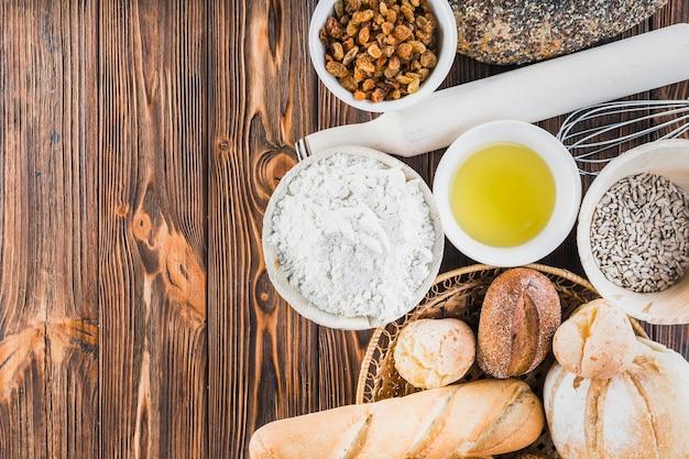 Panes recién hechos en casa con ingredientes en la mesa de madera