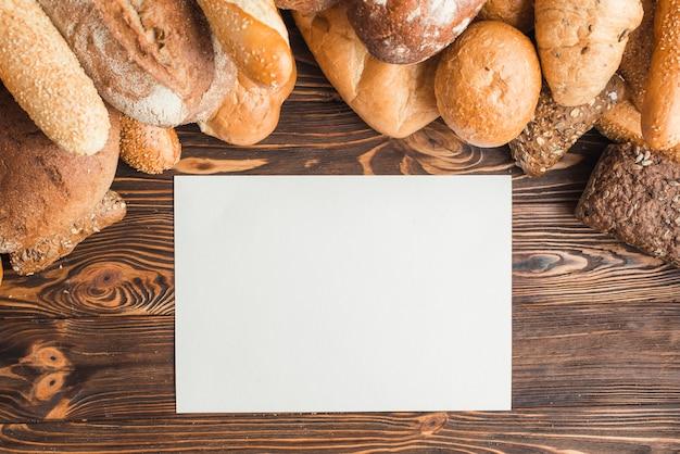 Panes recién horneados con papel blanco en blanco en el escritorio de madera
