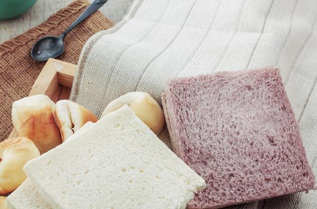Panes y tazas sobre mantel.