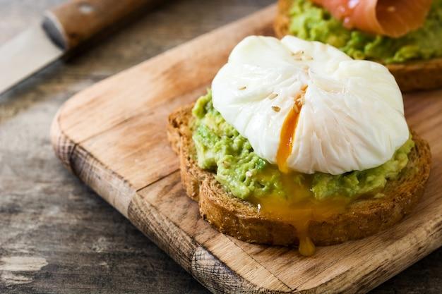 Panes tostados con huevos escalfados, aguacate en mesa de madera
