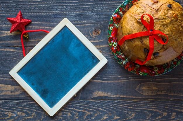 Panettone con fruta y decoración navideña, sobre una superficie de madera