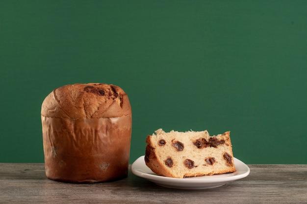 Panettone de pastel de chocolate navideño con una rebanada en un fondo de croma o chocotone de panetone