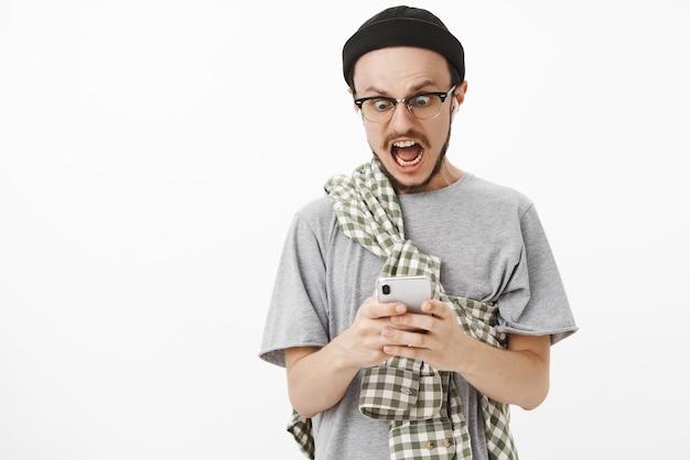 En pánico, chico sorprendido enviando una selección desnuda a mamá por error gritando y mirando tembloroso a la pantalla del teléfono inteligente con auriculares inalámbricos y gorro negro sobre una pared blanca
