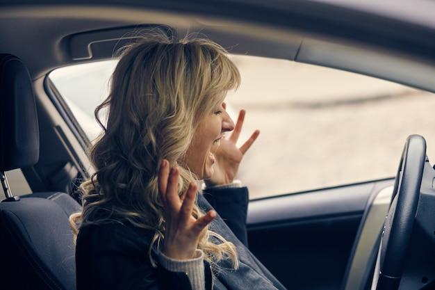 Pánico de hermosa mujer rubia en el coche. emergencia, accidente, camino, concepto de peligro