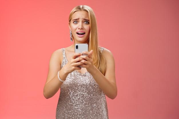 Pánico mujer sorprendida preocupada fotos filtradas internet mirada miedo ansioso ensanchar los ojos encogimiento preocupado asimiento smartphone sacudido sin palabras jadeando aterrorizados amigos descubren secreto, fondo rojo.