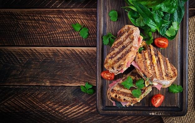 Panini sandwich a la plancha con jamón, tomate, queso y espinacas. delicioso desayuno o merienda. vista superior, espacio de copia, arriba
