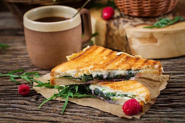 Panini sandwich con queso y hojas de mostaza. cafe mañanero. desayuno del pueblo