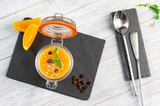 Panna cotta italiano tradicional con naranja y menta en un frasco.