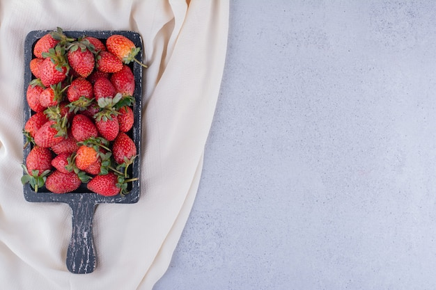 Paño blanco debajo de una bandeja de fresas apiladas sobre fondo de mármol. foto de alta calidad