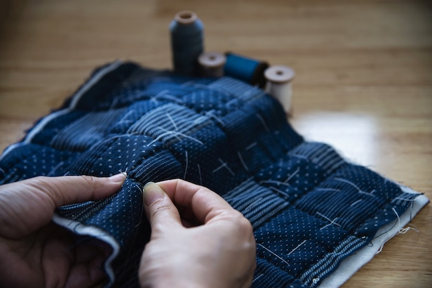 Paño de costura de mujer vintage a mano con bordado en mesa de madera - personas y concepto de bricolaje hecho a mano