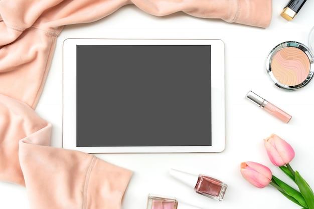 Paño de las mujeres, esmalte de uñas, cosmético y tableta en el fondo blanco, concepto de la belleza, visión superior, espacio de la copia.