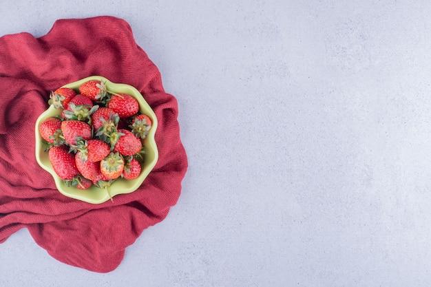 Paño rojo debajo de un cuenco de fresas sobre fondo de mármol. foto de alta calidad