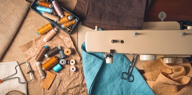 Panorama con accesorios de costura en el fondo de una máquina de coser borrosa.