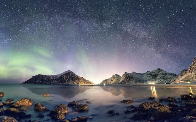 Panorama de la aurora boreal con la galaxia de la vía láctea sobre la montaña de nieve en la costa