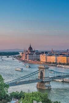 Panorama de budapest al atardecer hitos húngaros: parlamento puente de las cadenas y el río danubio en budapest