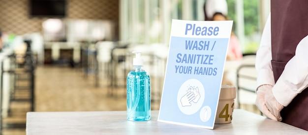 Panorama de cerca del stand de camarera asiática con gel de alcohol o desinfectante de manos con su señalización en el nuevo restaurante normal. nuevo concepto de normalidad e higiene para el estilo de vida del restaurante.