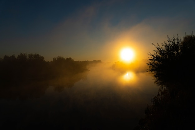 Panorama de la hermosa costa del lago brumoso en el momento del amanecer.