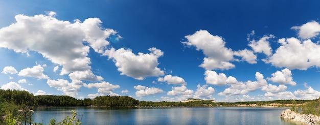 Panorama de un hermoso cielo azul con nubes blancas sobre el lago.