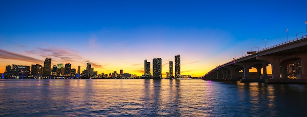 Panorama del horizonte de la ciudad de miami al atardecer con rascacielos urbanos y puente sobre el mar con reflejo